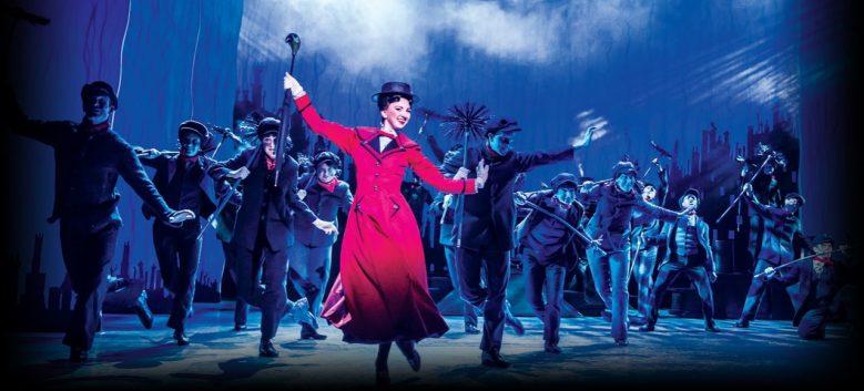 mary poppins de vestido mermelho, chapéu e guarda-chuva com atores dançando ao redor na peça de teatro mary poppins em londres