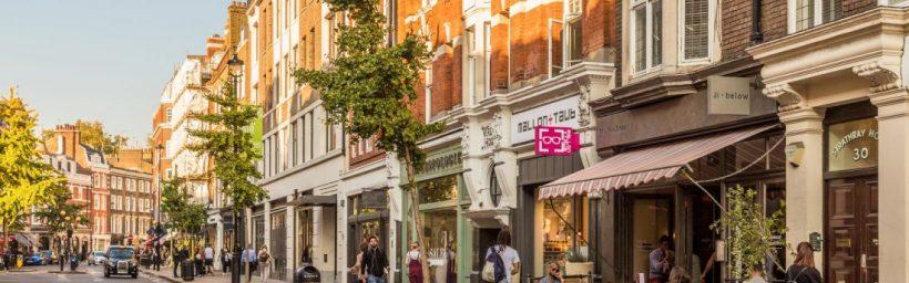 rua marylebone high street em londres com lojas, pessoas comprando e taxi preto ao fundo