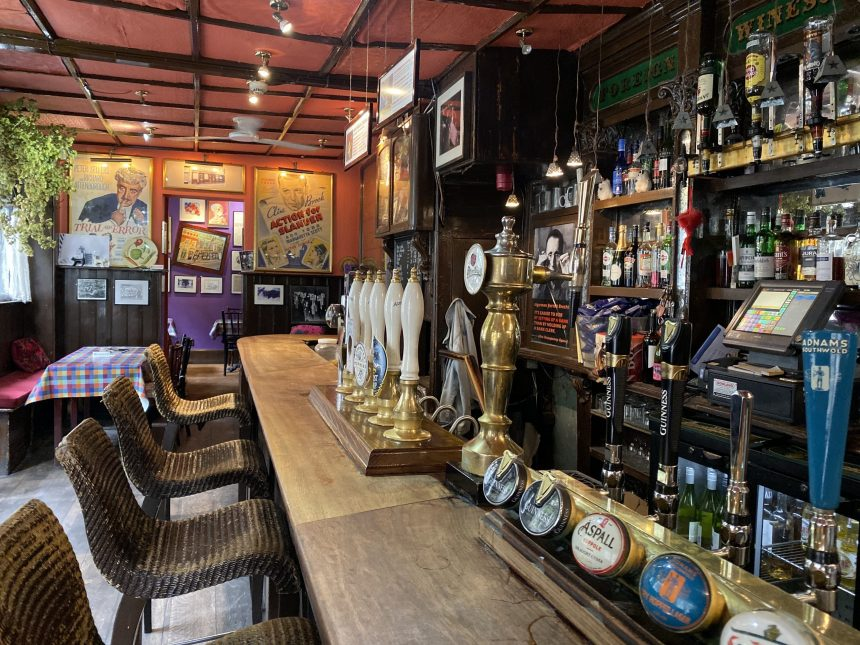 balcão de pub em londres com opções de cerveja ale e lager, teto sem decoração, quadros na parede e toalha de mesa colorida