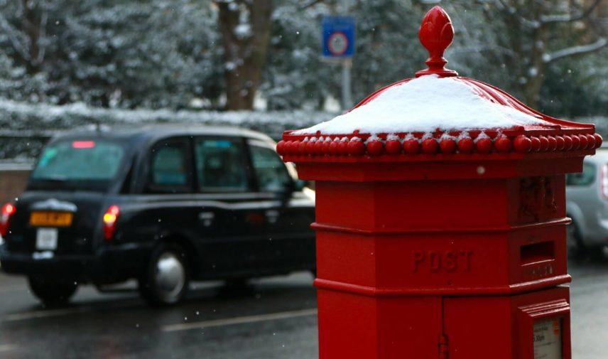 caixa de correio vermelha com um pouco de neve em cima e um taxi preto passando ao fundo em londres na inglaterra, durante um planejamento de viagem pra londres
