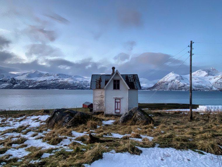 casinha com neve ao redor em frente a um lago no norte da noruega