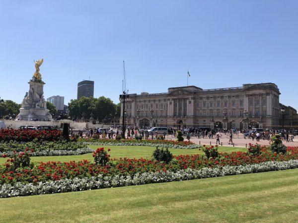 palacio de buckingham com bastante gente e jardim florido na frente e ceu azul num passeio guiado sobre a realeza britanica em londres