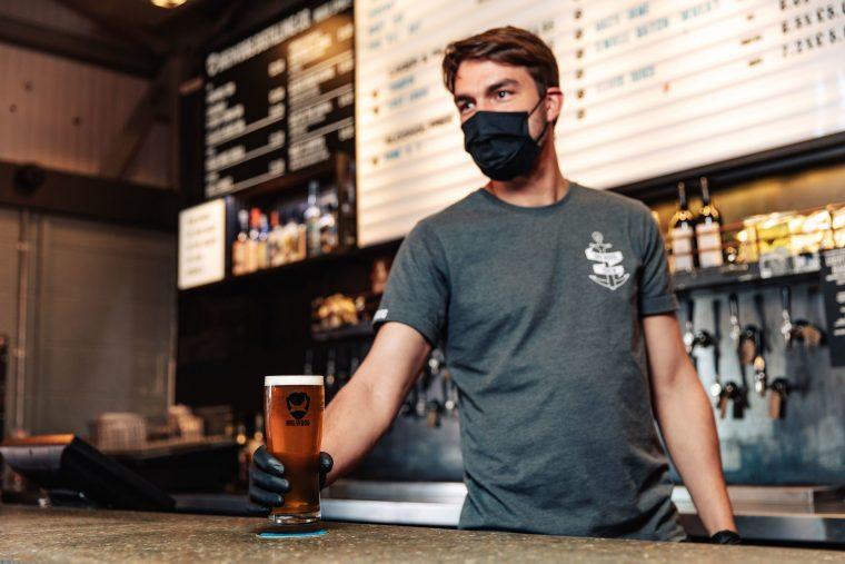 pint de cerveja ale da brewdog sendo servida por um bartender de mascara durante a pandemia do coronavirus em londres